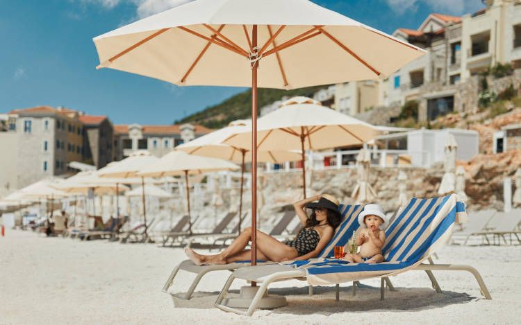 Mother and child enjoy hotel  beach at Montenegro Sea in Lustica Bay