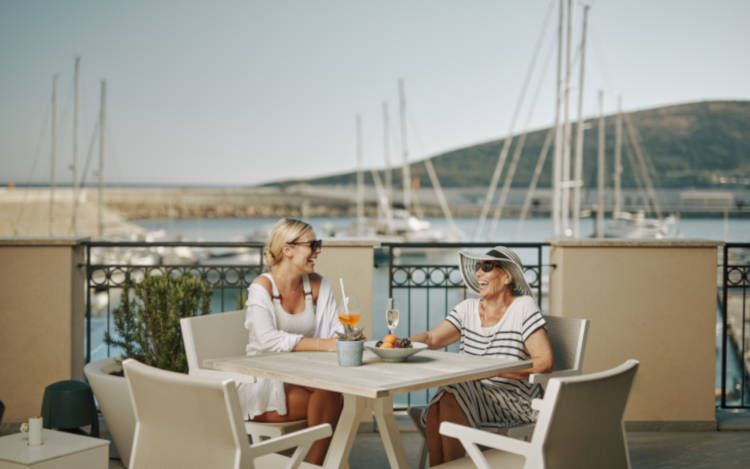 two female guests enjoying  adrink and afruit plate at outdoor pool bar in chedi lustica bay hote lin montenegro